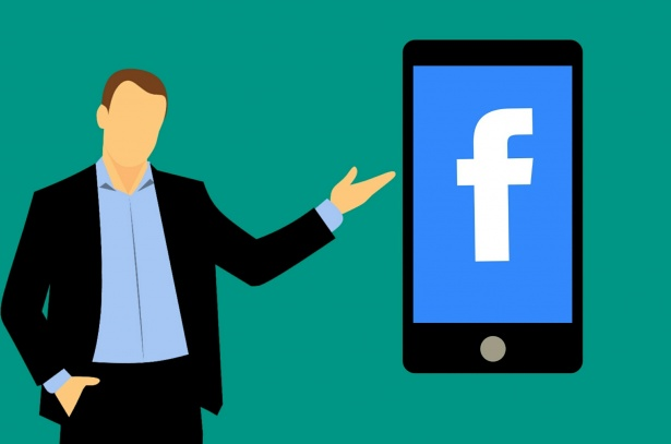 This is a stock image of a man pointing to a smartphone with the Facebook logo on display.